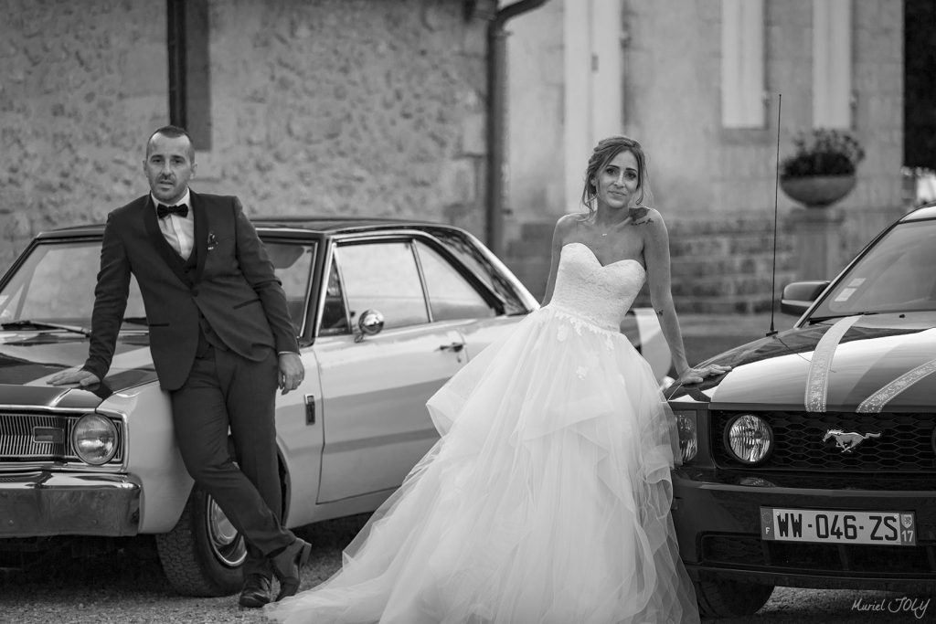 photographie noir et blanc de mariagecouple de mariés avec des voitures anciennes